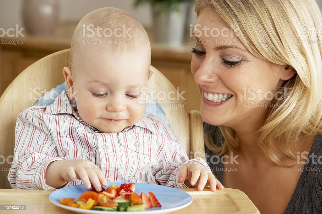 Mother Feeding Son In High Chair stock photo