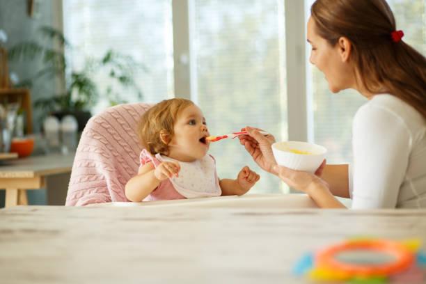 mutter füttert das baby - kinderstuhl und tisch stock-fotos und bilder