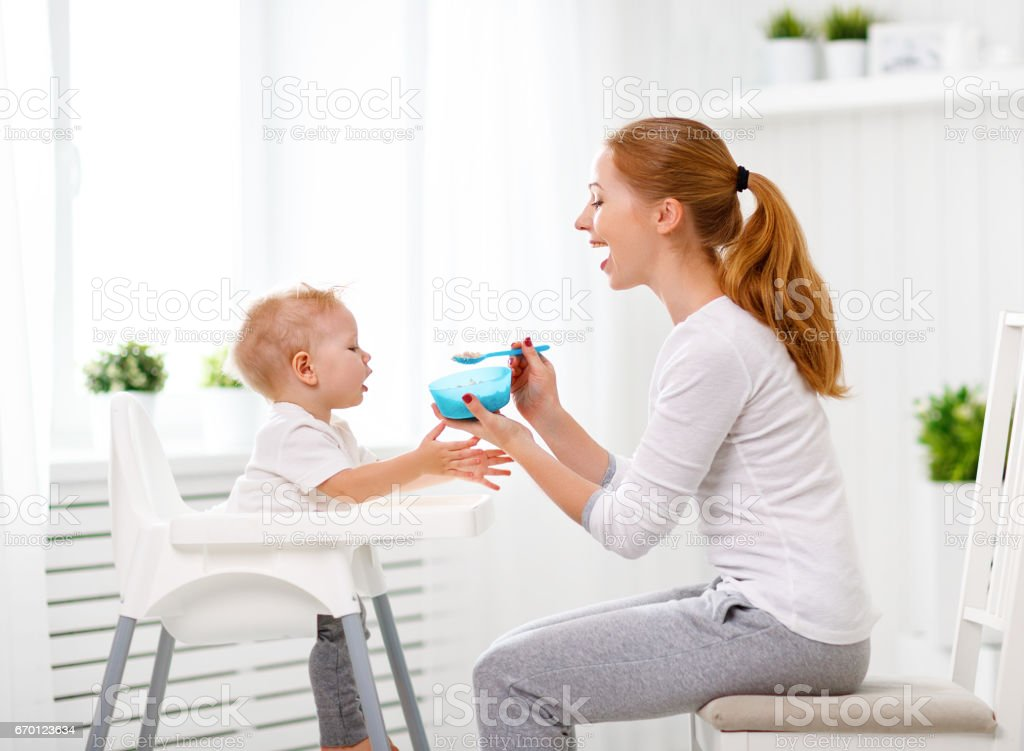 Mother feeds baby from spoon stock photo