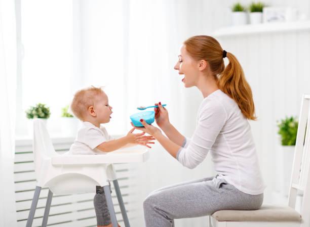 mother feeds baby from spoon - füttern stock-fotos und bilder