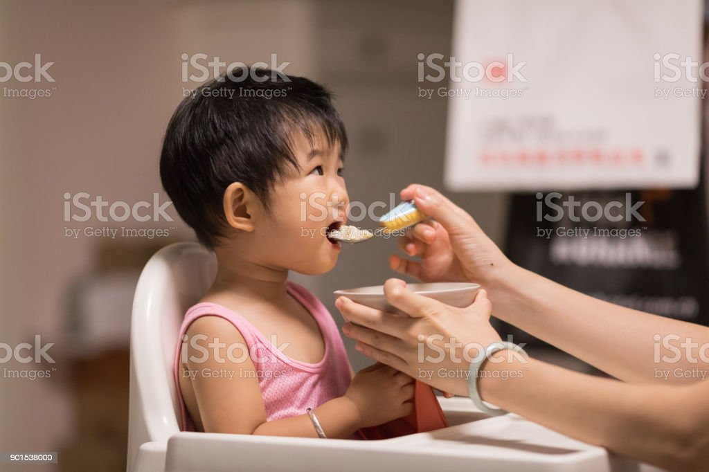 Mother feeds the baby to eating stock photo