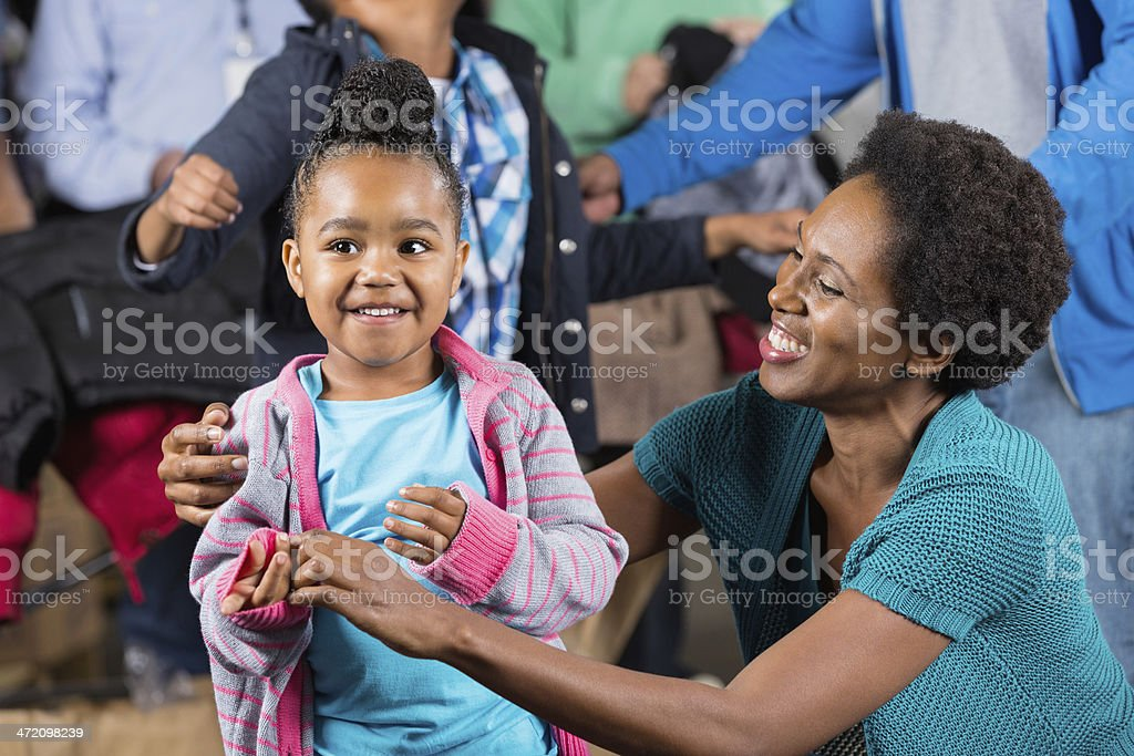 Mother finding donated clothing for kids at winter coat drive royalty-free stock photo
