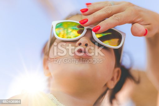 istock Mother fixing her daughter's sunglasses 682408984