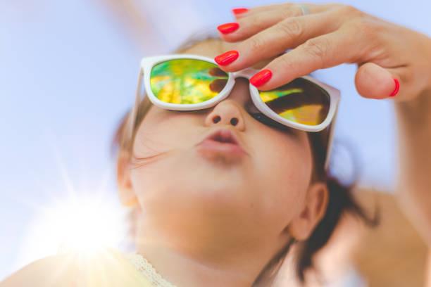 mutter, die festsetzung ihrer tochter sonnenbrillen - sonnenbrille kleinkind stock-fotos und bilder