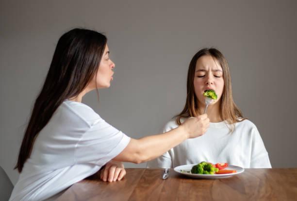 mother forces her teen daughter to eat healthy food feeding her broccoli with fork. food waste. no vegan diet concept. no choice - desperdício alimentar imagens e fotografias de stock