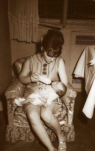 Vintage black and white toned image of a mom feeding her baby.