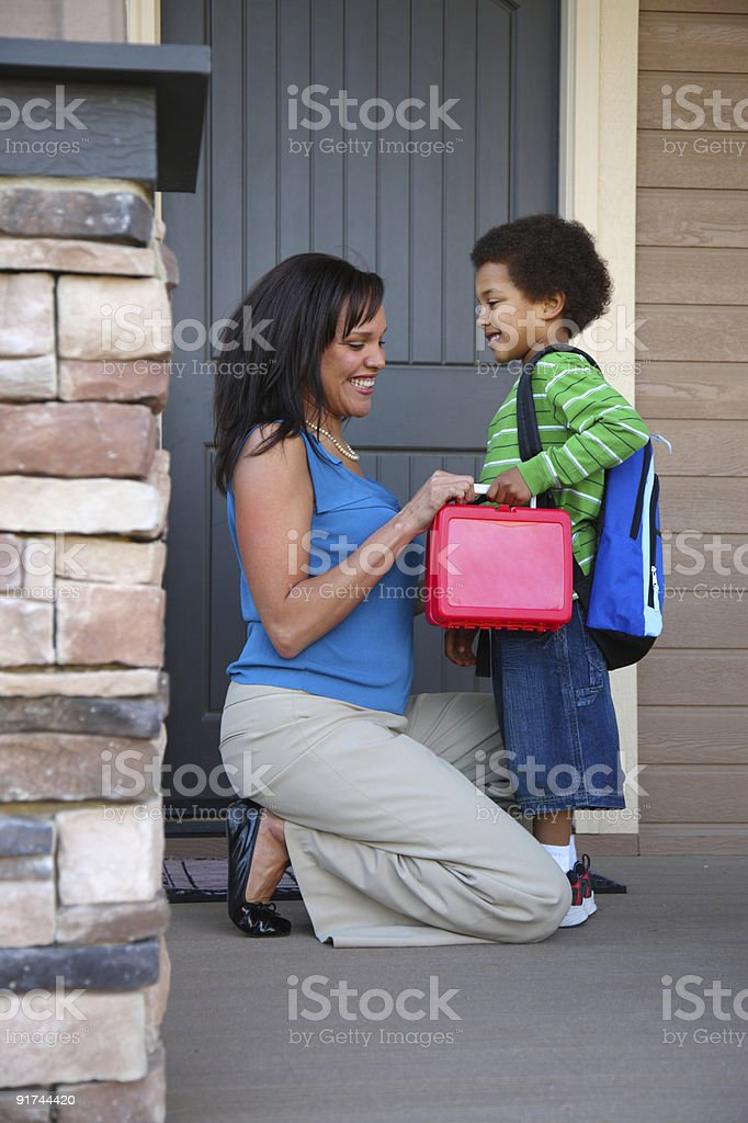 Mother gets child ready for first day of school stock photo