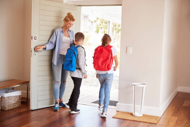 mother getting children ready to leave house for school - leaving stock photos and pictures