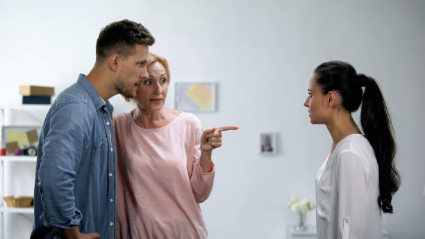 Mother getting on son side in conflict with wife, interference in relationship stock photo
