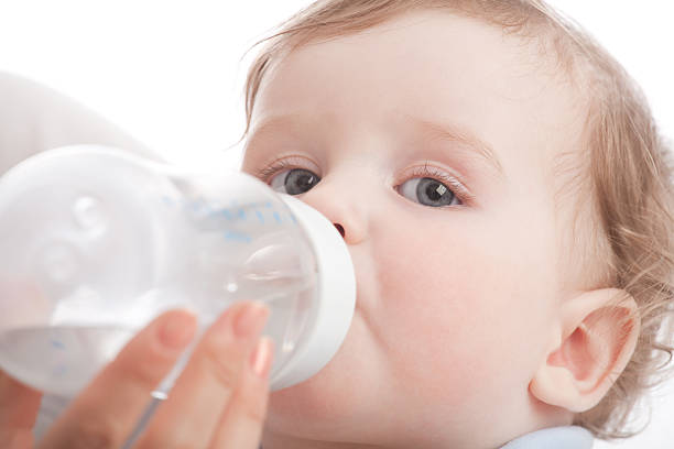 Mother give drink her son by feeding bottle stock photo