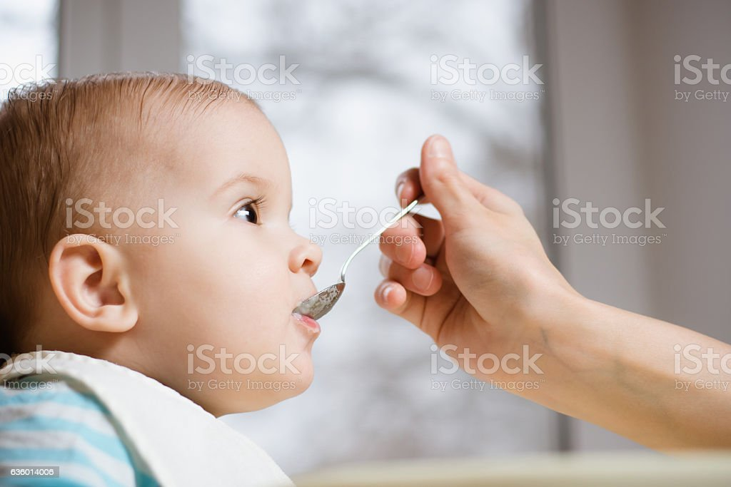 Mother gives baby food from a spoon - foto de acervo