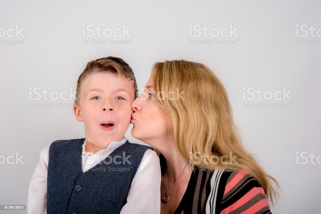 Mother gives her 9 year old son a kiss . stock photo