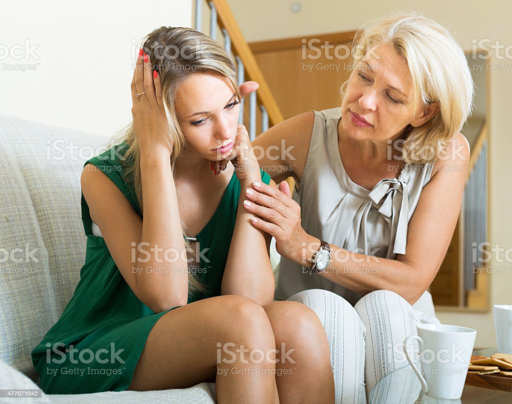Mother gives solace to daughter stock photo