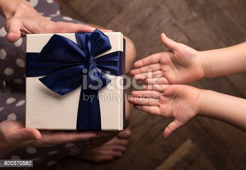 istock Mother giving a big gift boxes to her kid 620370582