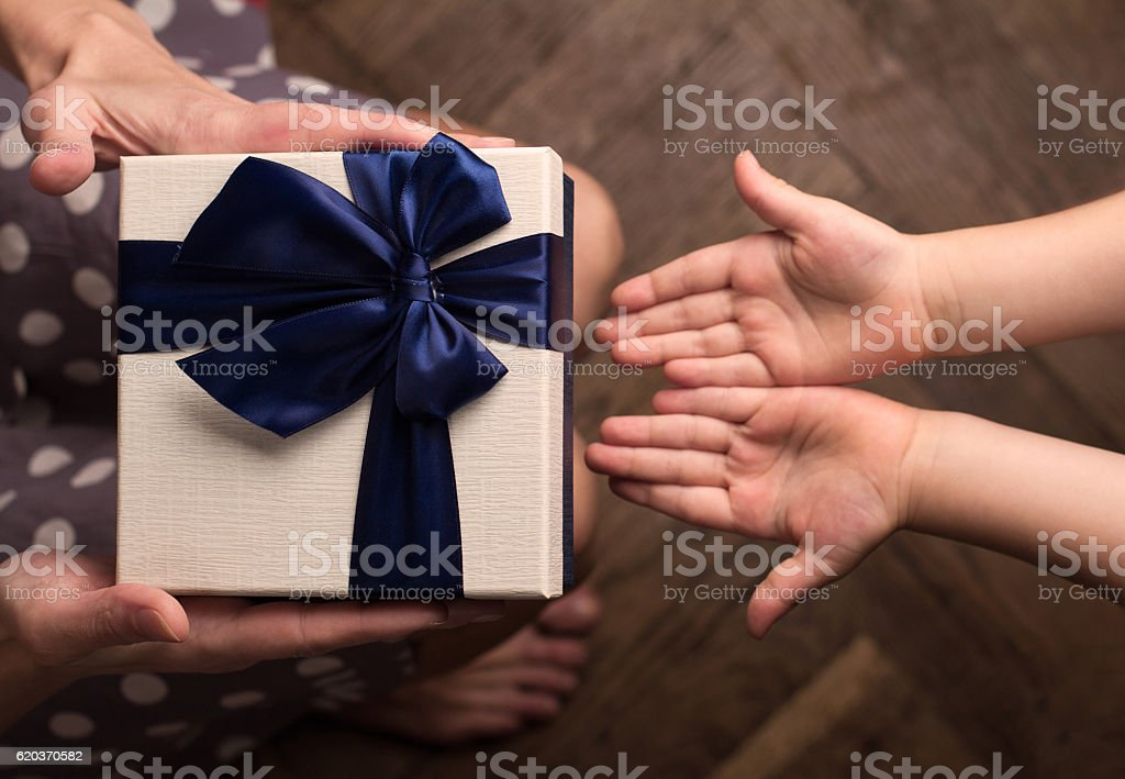 Mother giving a big gift boxes to her kid stock photo