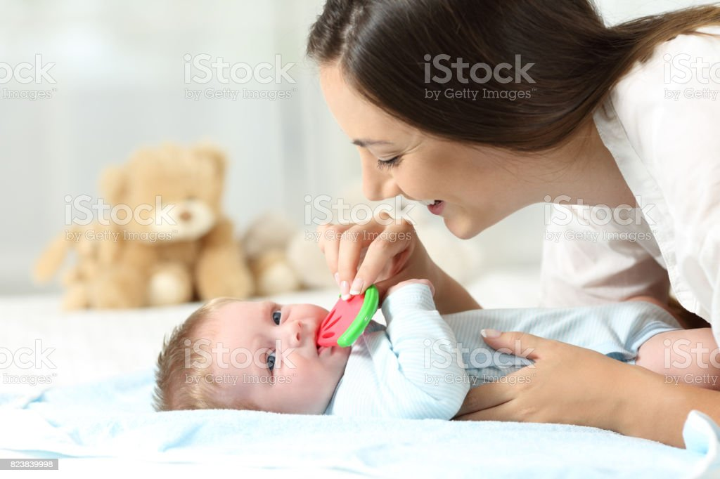 Mother giving a bitter to her baby stock photo