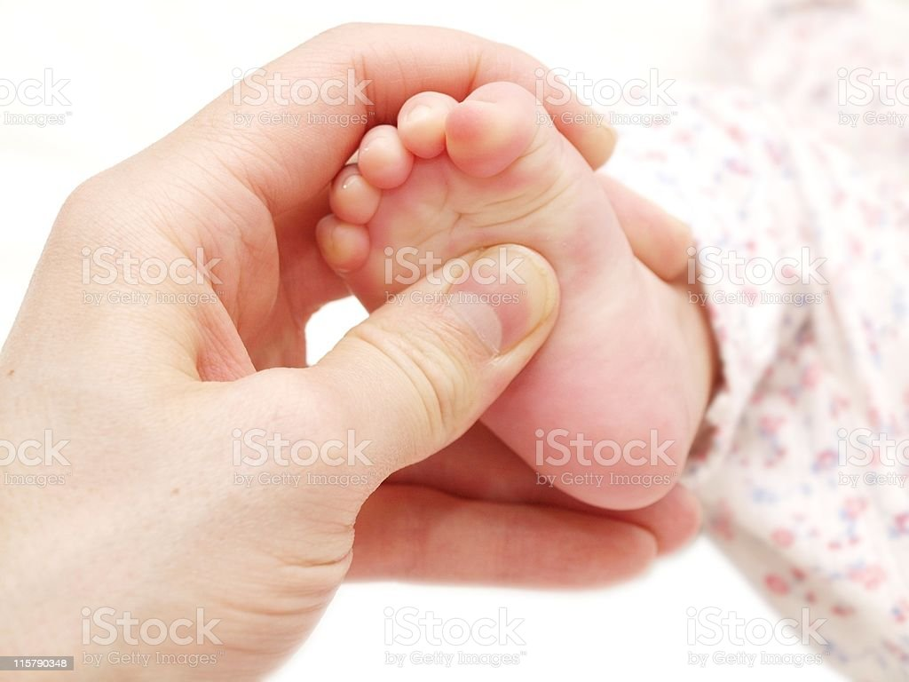 A mother giving a tender massage to a baby's foot royalty-free stock photo