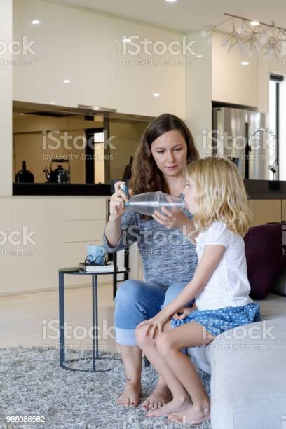 Mother Giving Asthma Treatment To Asthmatic Daughter - Fotografias de stock e mais imagens de 6-7 Anos