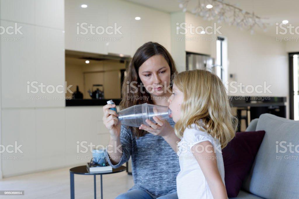 Mor ger astmabehandling till astmatiska dotter - Royaltyfri 6-7 år Bildbanksbilder