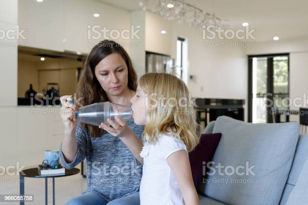 Mother Giving Asthma Treatment To Asthmatic Daughter — стоковые фотографии и другие картинки 6-7 лет