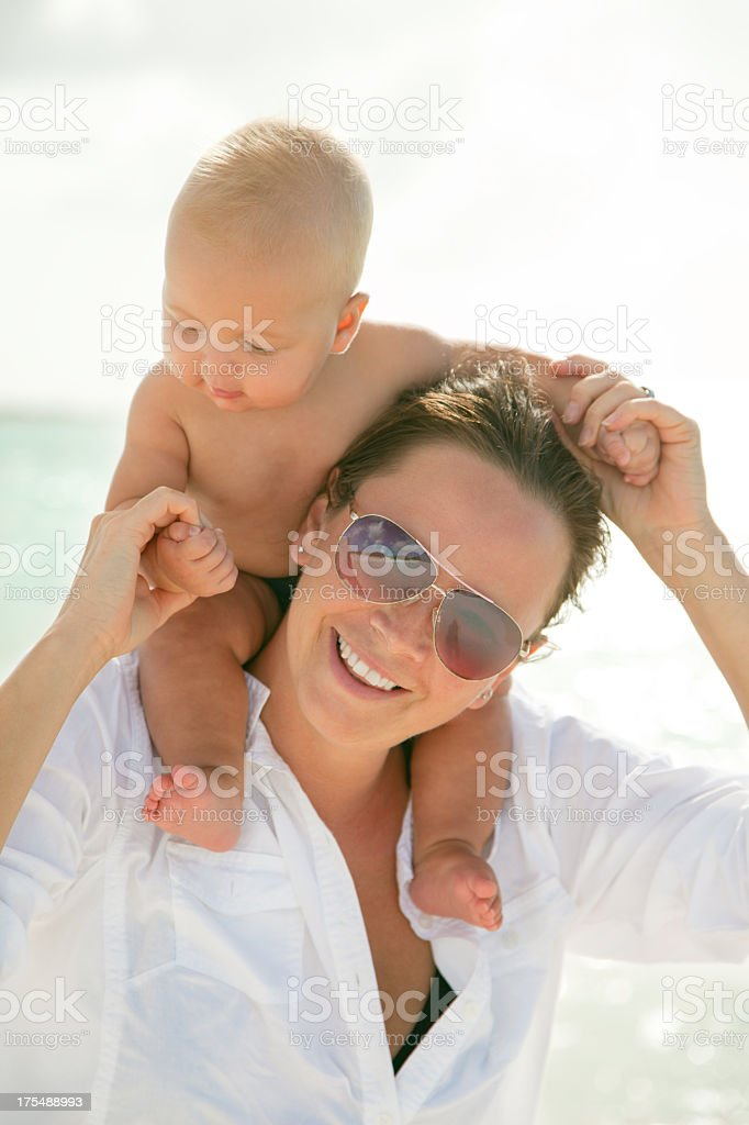 mother giving baby piggyback ride at a tropical Caribbean beach stock photo