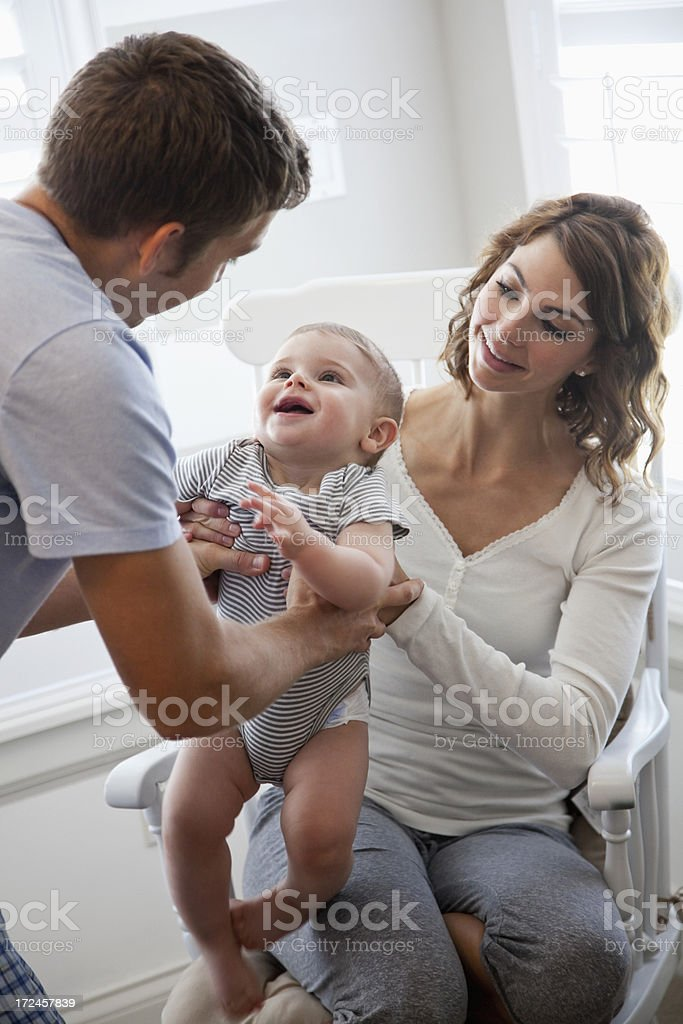 Mother giving baby to father stock photo