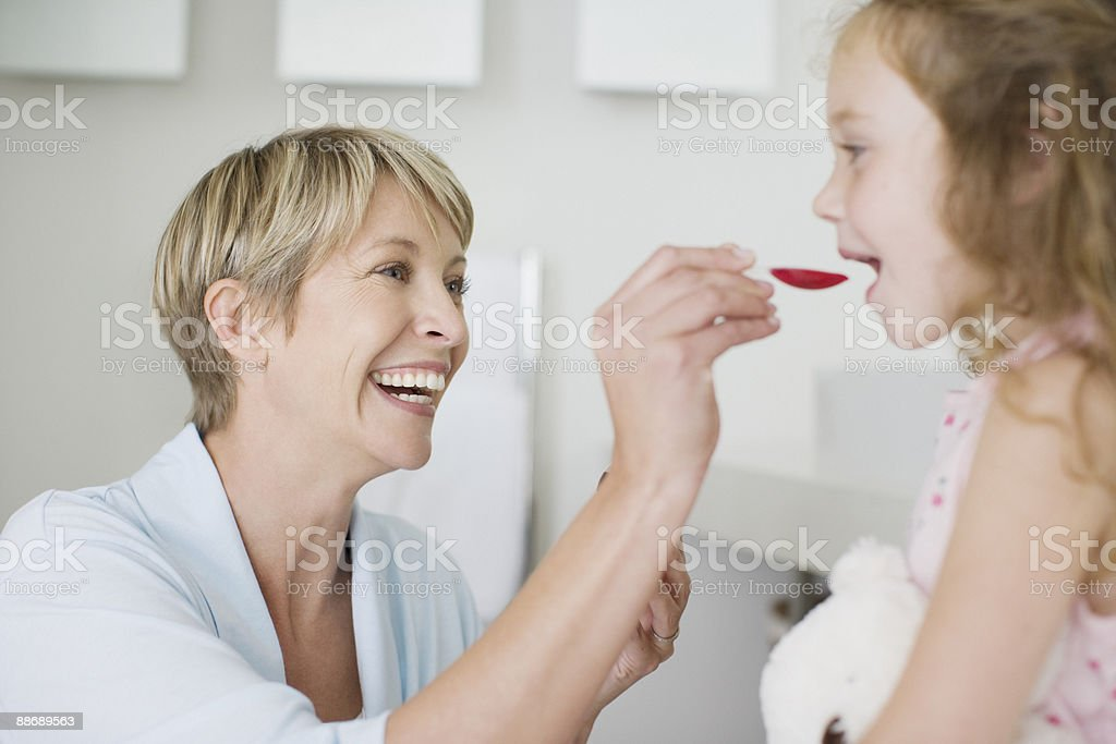 Mother giving daughter medicine royalty-free stock photo