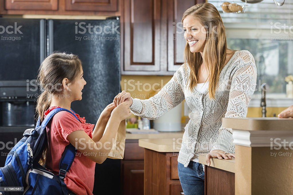 Mother giving daughter sack lunch before leaving for school stock photo
