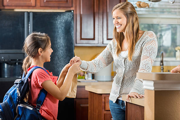 mother giving daughter sack lunch before leaving for school - little girls giving head stock photos and pictures