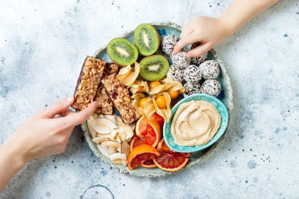 母親給幼兒提供健康的素食主義者甜點零食。兒童健康糖果的概念。蛋白質燕麥棒, 自製的生能量球, 腰果黃油, 烤椰子片, 水果拼盤 - 健康飲食 個照片及圖片檔