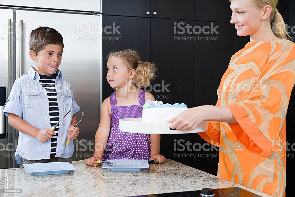 A mother giving her children cake 免版稅 stock photo