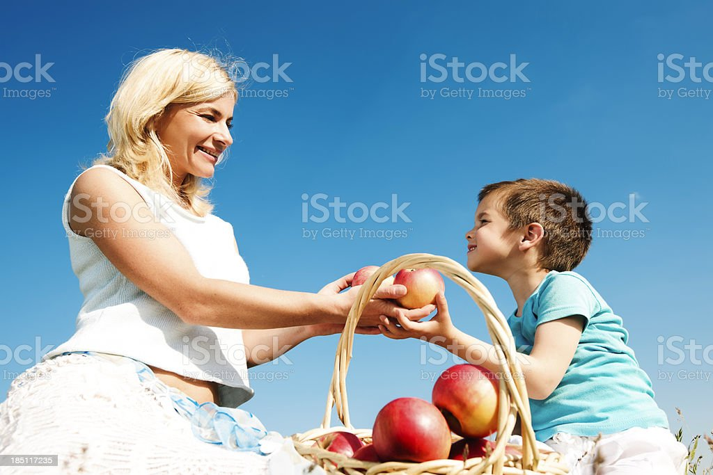 Mother giving her cute son apples. royalty-free stock photo