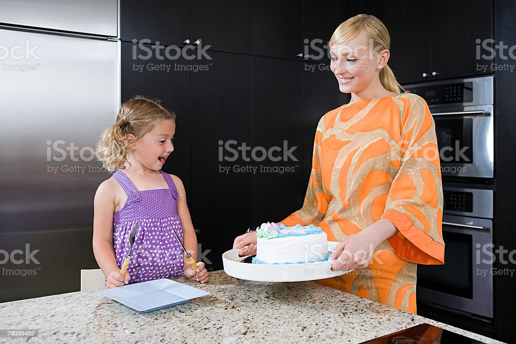 A mother giving her daughter a cake 免版稅 stock photo