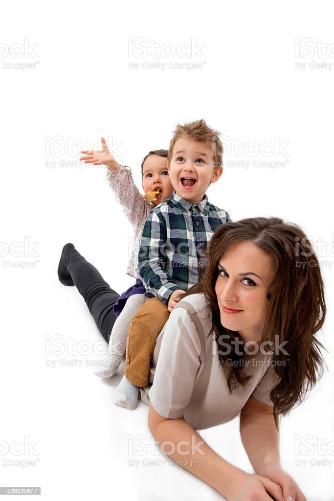 Mother giving her daughter and son piggyback ride royalty-free stock photo