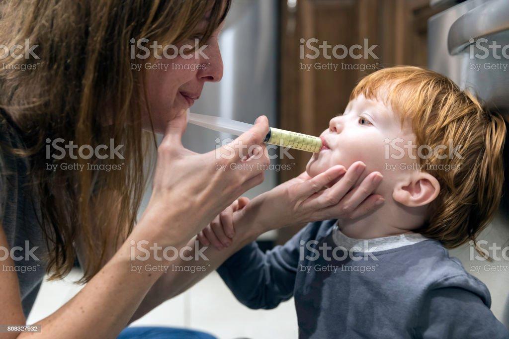 Madre dando penicilina medicina enferma su bebé niño - foto de stock