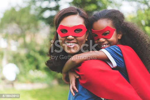 Side view of smiling woman giving piggyback ride to daughter in back yard. Happy mother and girl are wearing red superhero costume. They are spending leisure time.