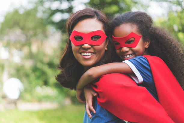 mother giving piggyback to daughter in costume - super hero stock pictures, royalty-free photos & images