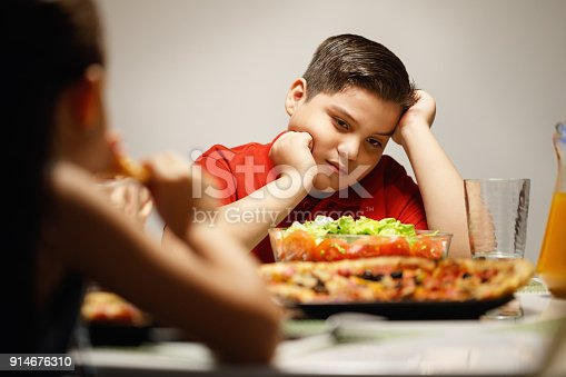 Hispanic family with mom, fat son and daughter having dinner at home, eating salad and pizza. Latino people with mother, overweight boy and girl during meal.
