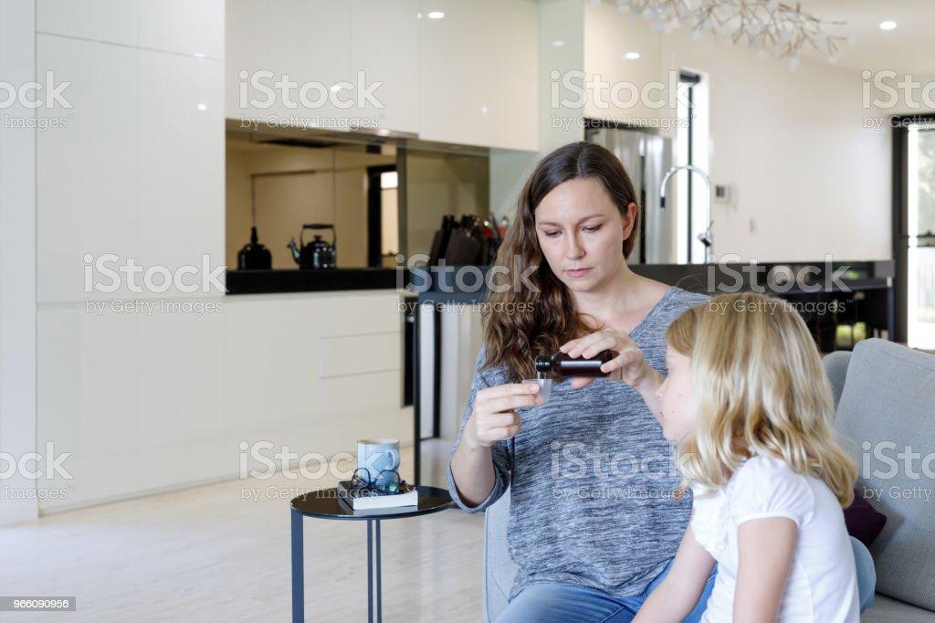 Mor ger sjuka dotter medicin - Royaltyfri 6-7 år Bildbanksbilder