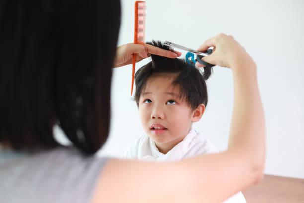 coupe de fils donnant mère - couper les cheveux photos et images de collection