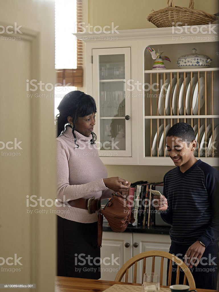Mother giving son (12-13) pocket money in kitchen royalty free stockfoto