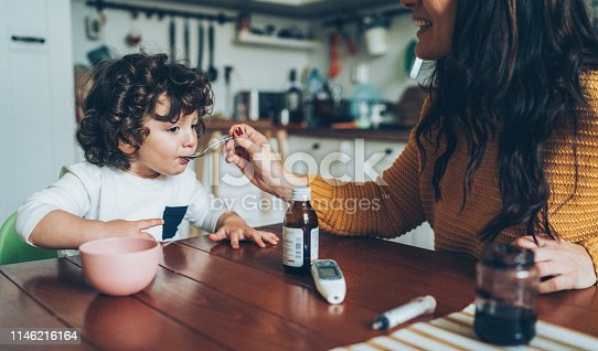 Mother giving syrup to her cute little son