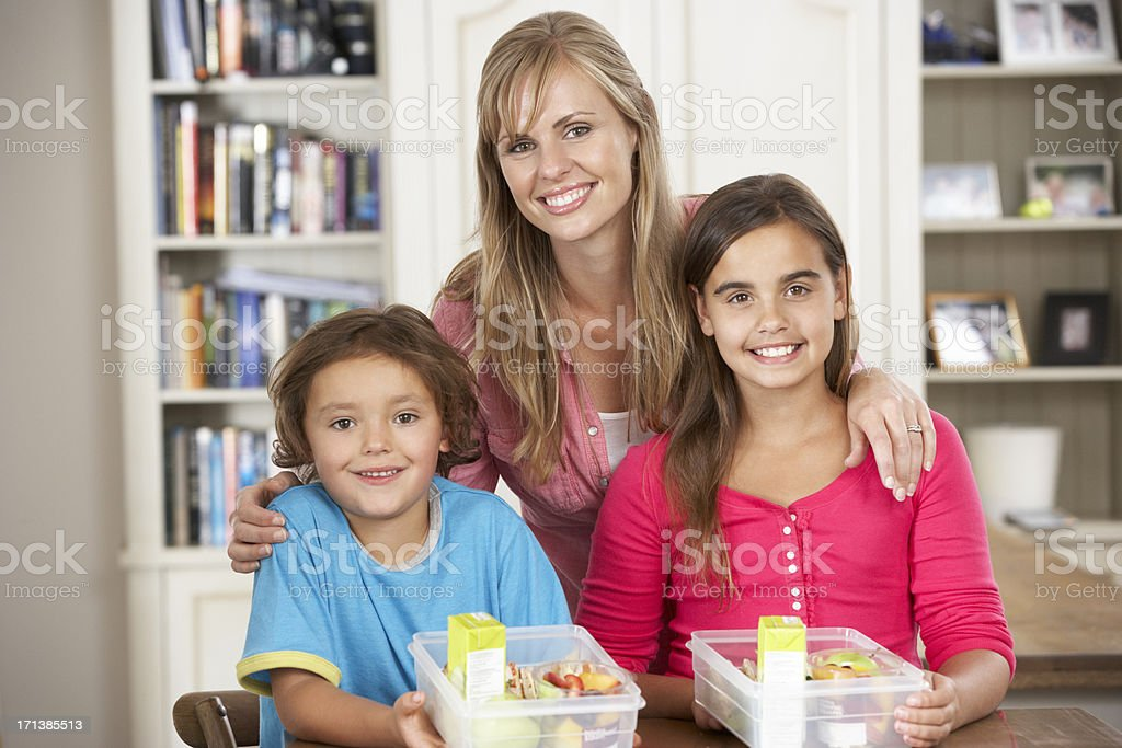 Mother Giving Two Children Healthy Lunchboxes In Kitchen royalty-free stock photo