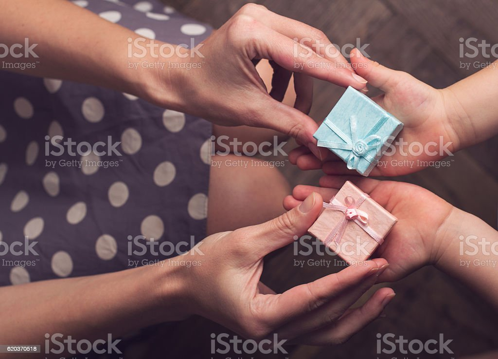 Mother giving two small gift boxes to her kid zbiór zdjęć royalty-free