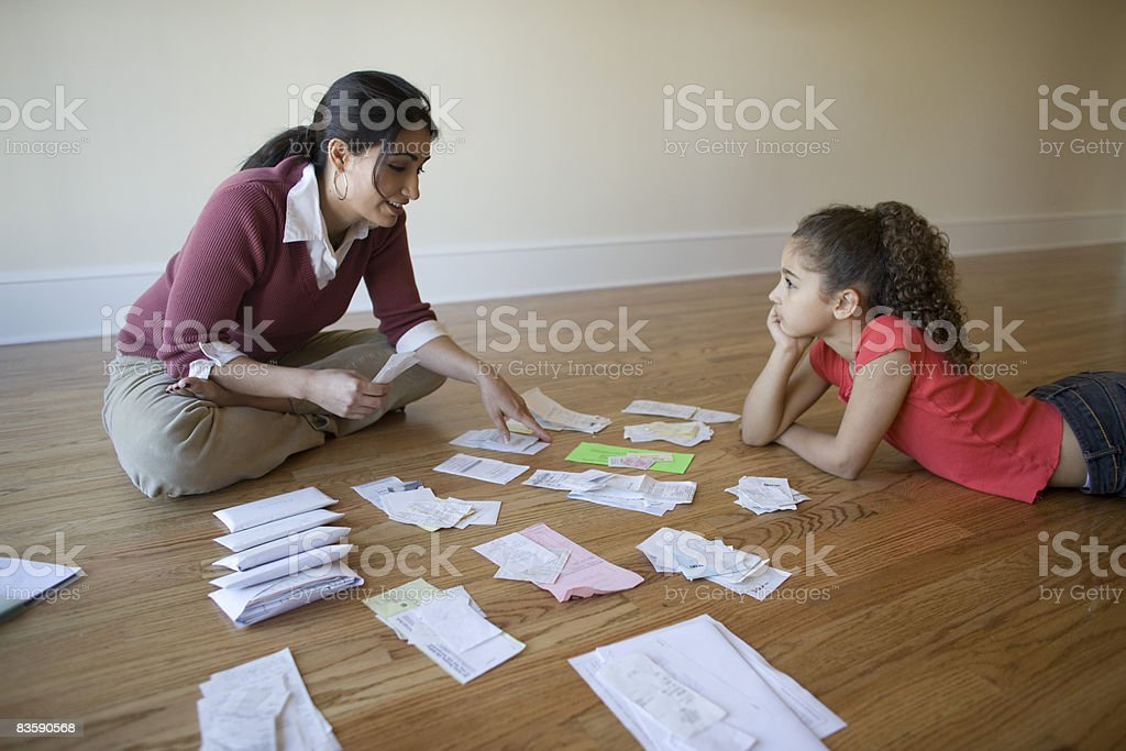 Mother going through bills with daughter stock photo