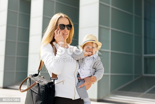 istock Mother going to work and talking on the phone with baby in her hands 852047084