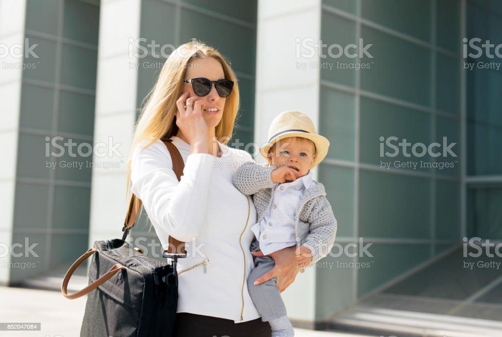 Mère aller travailler et parler au téléphone avec le bébé dans ses mains - Photo