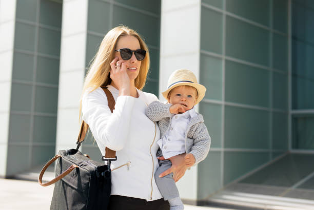 Mother going to work and talking on the phone with baby in her hands stock photo