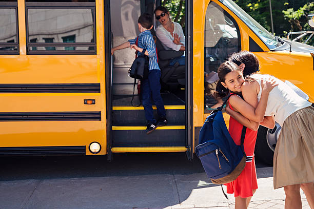 Mother greeting elementary age girl getting off school bus. – Foto