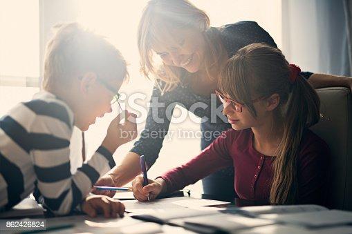 862426824 istock photo Mother halping kids to do homework 862426824